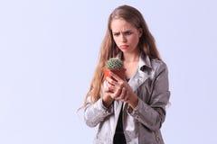 Muchacha trastornada de los jóvenes que presenta con el cactus en un fondo gris Imágenes de archivo libres de regalías