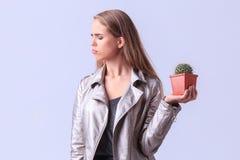 Muchacha trastornada de los jóvenes que presenta con el cactus en un fondo gris Imagen de archivo