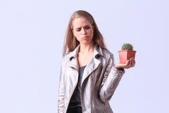 Muchacha trastornada de los jóvenes que presenta con el cactus en un fondo gris Fotografía de archivo