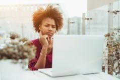 Muchacha trastornada del africano con el ordenador portátil en barra de la calle Fotografía de archivo