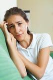 Muchacha trastornada en el sofá en casa Foto de archivo