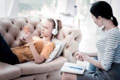 Muchacha trastornada que escucha la música durante la asistencia del psicólogo Fotografía de archivo libre de regalías