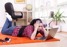 Muchacha trastornada que mira el ordenador portátil Imagen de archivo
