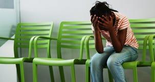 Muchacha trastornada que se sienta en silla en pasillo del hospital metrajes