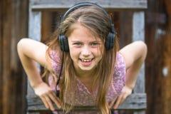Muchacha traviesa con los auriculares al aire libre Fotos de archivo libres de regalías