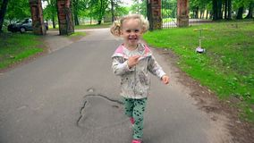 Muchacha traviesa de risa que corre en el camino del parque El niño lindo del niño se divierte al aire libre almacen de metraje de vídeo
