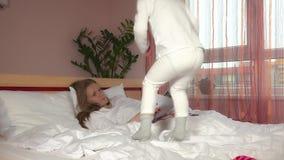 Muchacha traviesa del niño que salta en cama mientras que su mujer de la madre leyó la revista almacen de metraje de vídeo