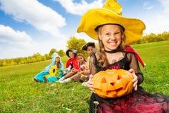 Muchacha traviesa en vestido de la bruja con la calabaza de Halloween Imagen de archivo libre de regalías