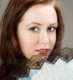 Muchacha triguena atractiva con el ventilador Imagen de archivo