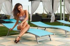 Muchacha triguena atractiva en la piscina Fotos de archivo