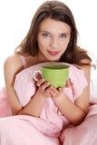 Muchacha triguena bastante adolescente que bebe algo caliente Fotos de archivo libres de regalías
