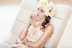 Mujer triguena bonita con el sombrero fabuloso de la flor Imagenes de archivo