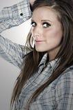 Muchacha triguena hermosa en camisa controlada Imagen de archivo