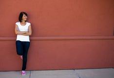 Muchacha triguena hermosa que espera en banco Foto de archivo libre de regalías