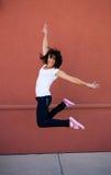 Muchacha triguena joven hermosa que salta para la alegría Imagenes de archivo
