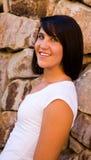 Muchacha triguena joven hermosa que se inclina en la pared de la roca Foto de archivo