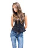 Muchacha triguena joven magnífica que presenta en pantalones vaqueros. Foto de archivo