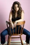 Muchacha triguena que se sienta en silla Imagen de archivo libre de regalías