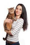 Muchacha triguena sonriente hermosa y su gato del jengibre sobre los vagos blancos Fotos de archivo