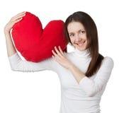 Muchacha triguena sonriente que lleva a cabo el corazón rojo Foto de archivo libre de regalías