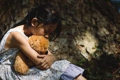 Muchacha triste adorable con el oso de peluche Imágenes de archivo libres de regalías