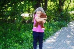 Muchacha triste adorable con el oso de peluche en parque Imagen de archivo