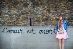 Muchacha triste cerca de la pared con palabras Fotos de archivo libres de regalías