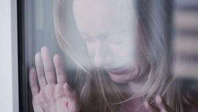 Muchacha triste cerca de la ventana mujer del plachet rasgones en schekah almacen de video