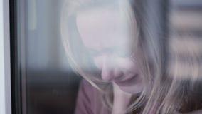 Muchacha triste cerca de la ventana mujer del plachet rasgones en schekah almacen de metraje de vídeo