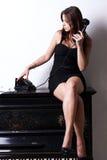 Muchacha triste cerca del piano con el teléfono retro Foto de archivo
