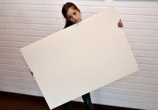 Muchacha triste con el cartel en blanco Foto de archivo libre de regalías
