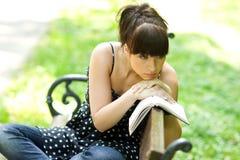 Muchacha triste con el libro Imagen de archivo