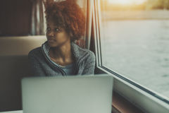 Muchacha triste con el ordenador portátil en cabina de la nave Fotos de archivo libres de regalías