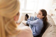 Muchacha triste con el smartphone que mira a la madre en casa Fotos de archivo libres de regalías