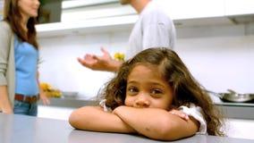 Muchacha triste con los brazos doblados mientras que padres que pelean almacen de video