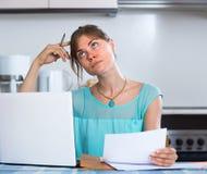 Muchacha triste con los documentos en la cocina Imagen de archivo