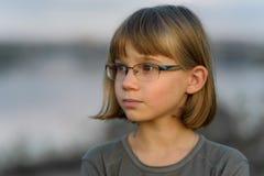 Muchacha triste del adolescente con el pelo rubio corto y los ojos azules contra el cielo de la tarde Imagen de archivo