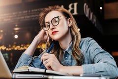 Muchacha triste del estudiante que se sienta en café delante del ordenador portátil que se prepara para los exámenes La mujer tom fotos de archivo