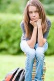 Muchacha triste del estudiante que se sienta en los libros Imagenes de archivo