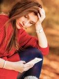 Muchacha triste del trastorno con el teléfono móvil en parque del otoño Fotografía de archivo libre de regalías