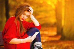 Muchacha triste del trastorno con el teléfono móvil en parque del otoño Imagen de archivo