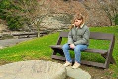 Muchacha triste en banco Foto de archivo