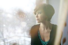Muchacha triste en el alféizar que mira hacia fuera la ventana Imagen de archivo libre de regalías