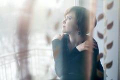 Muchacha triste en el alféizar que mira hacia fuera la ventana Fotos de archivo libres de regalías