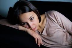 Muchacha triste en el retrato de la cara del sofá en la noche Fotos de archivo