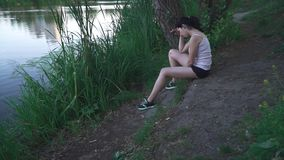 Muchacha triste en la orilla del río almacen de video