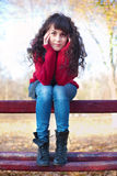 Muchacha triste en un parque en banco Imagenes de archivo