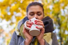 Muchacha triste enferma con la bebida caliente y medicina en el parque Otoño tim Imagenes de archivo