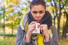 Muchacha triste enferma con la bebida caliente y medicina en el parque Otoño tim Imágenes de archivo libres de regalías