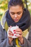Muchacha triste enferma con la bebida caliente y medicina en el parque Otoño tim Foto de archivo